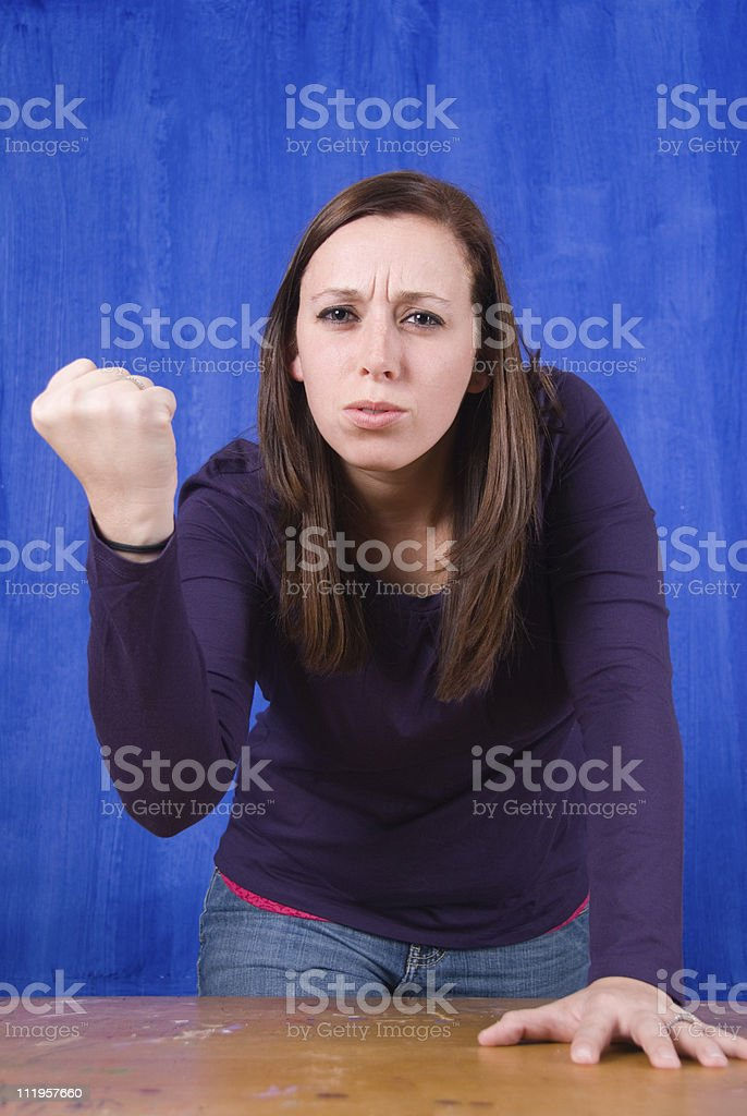 Young woman leaning on the table with threatening fist royalty-free stock photo