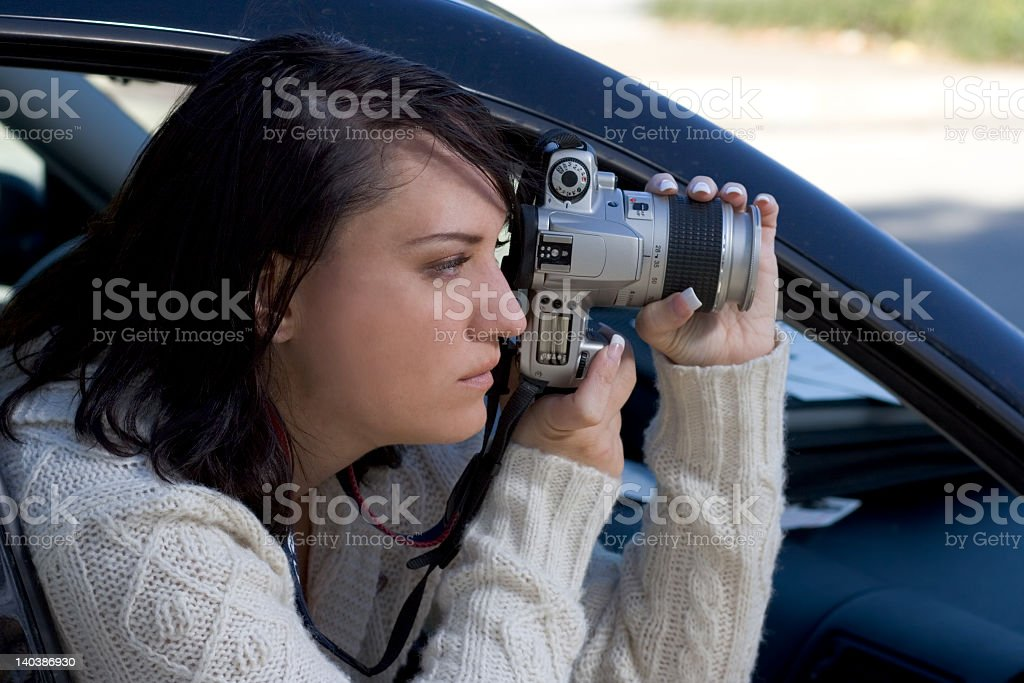 Young woman leaning out passenger window taking picture stock photo