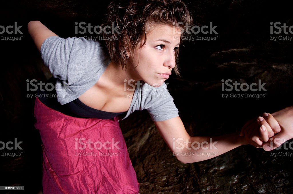 Young Woman Leaning Over and Walking Through Caves stock photo