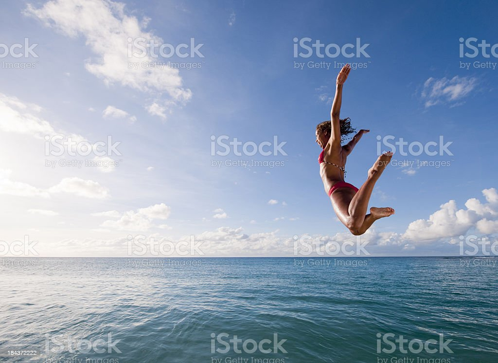 Young woman leaping into the sea royalty-free stock photo