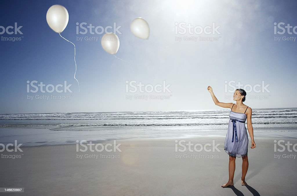 Young woman letting go of balloons on beach stock photo