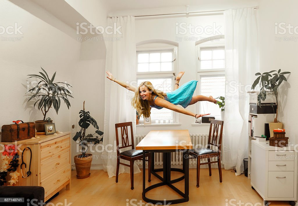 Young woman levitating in study stock photo
