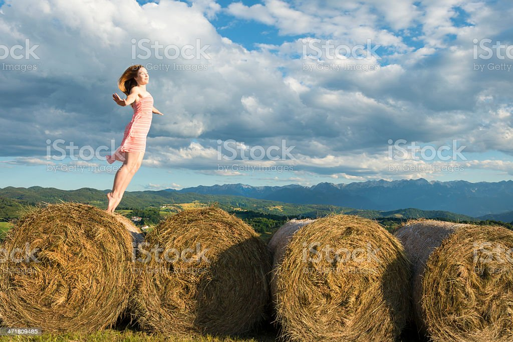 Young Woman Levitating on Bale Silage royalty-free stock photo