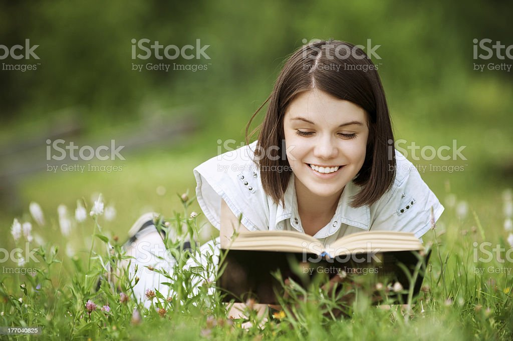 Young woman lies on grass and reads book royalty-free stock photo