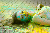 Young woman lies on the pavement with color powder
