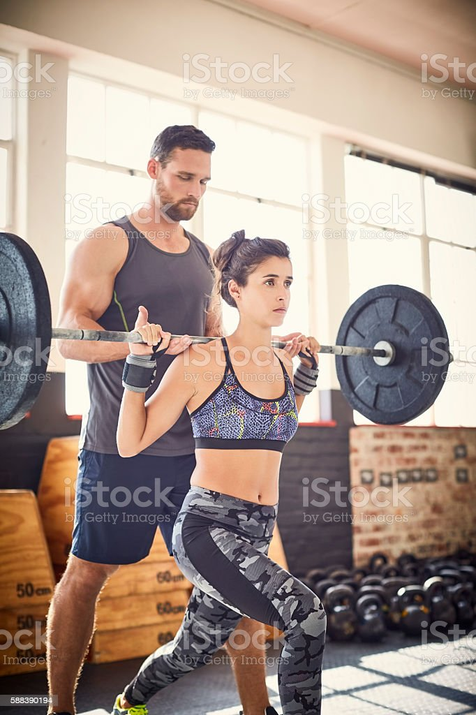 Young woman lifting barbell while coach assisting her in gym stock photo