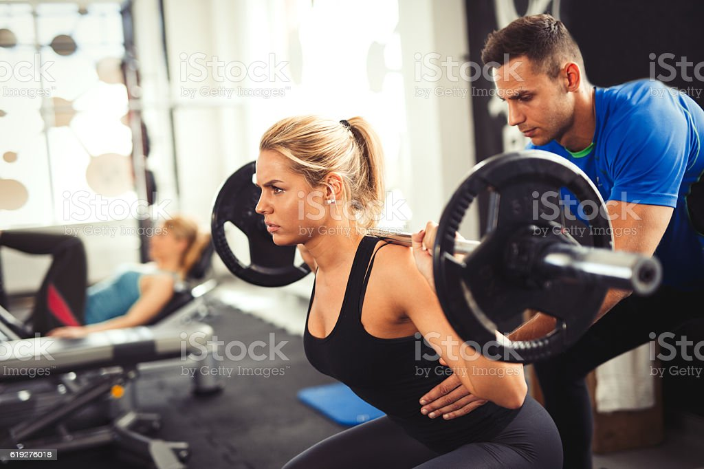 Young woman lifting barbell with her personal trainer assistance. stock photo