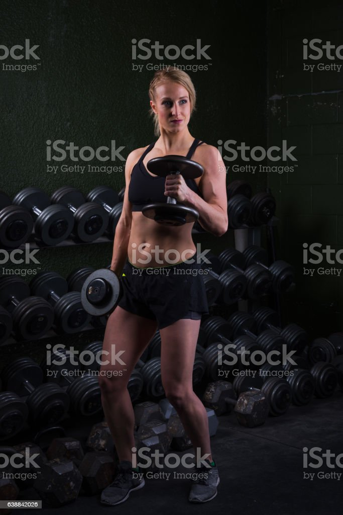 Young woman lifting free weights at a gym. stock photo