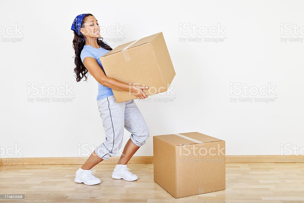 Young woman lifting heavy box stock photo