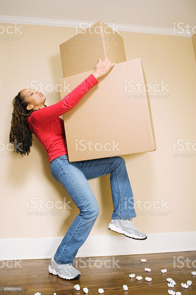 Young woman lifting large boxes stock photo