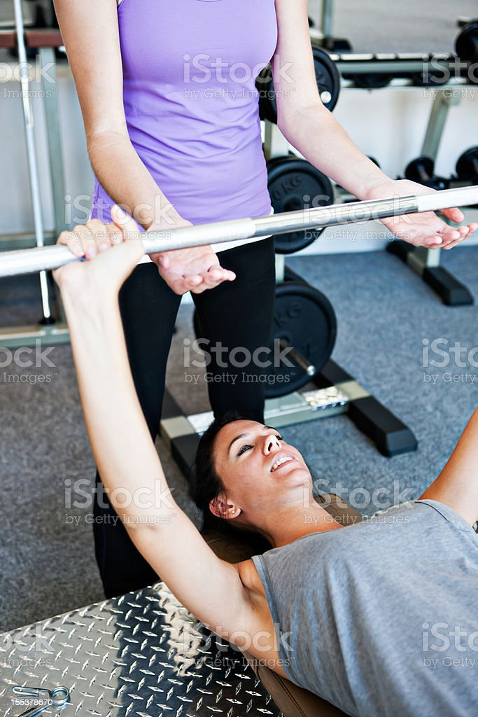 Young woman lifting weights as friend spots for her stock photo