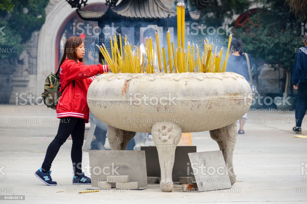 Young woman lights candle at Buddhist monastery stock photo