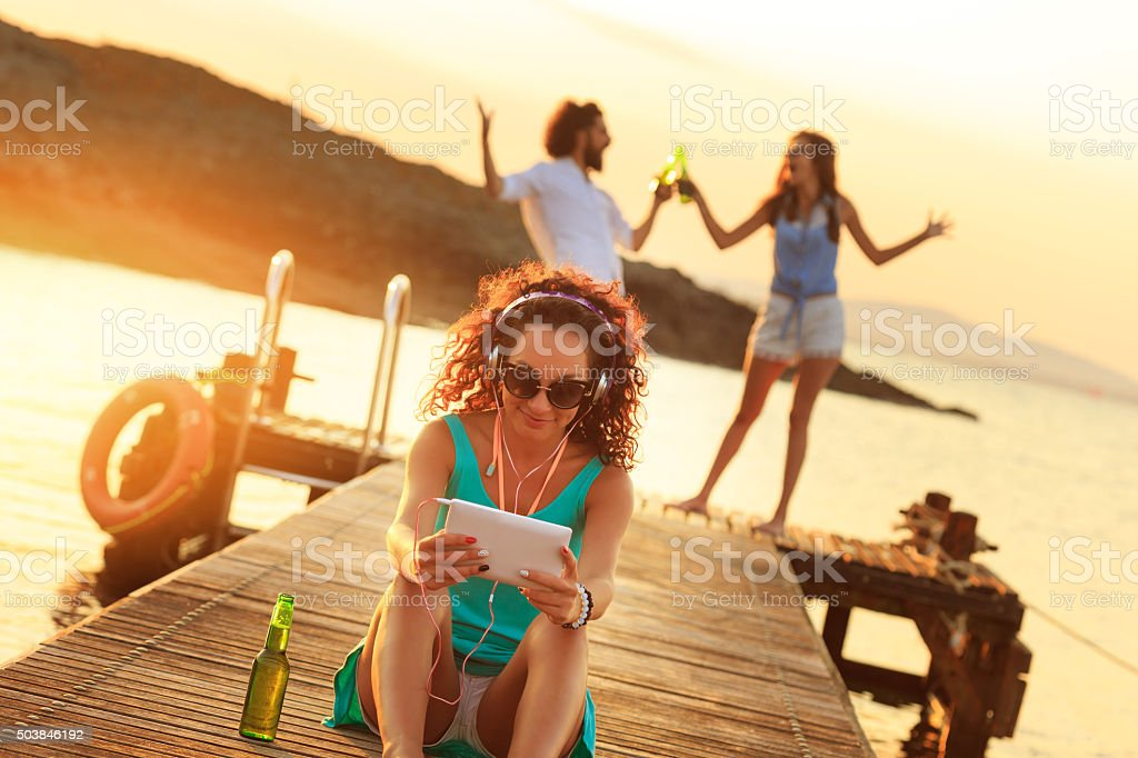 Young woman listening music on digital tablet stock photo