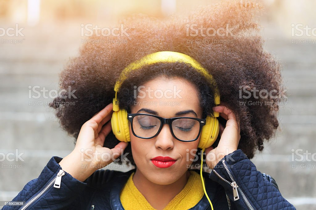 Young woman listening music on stairs stock photo