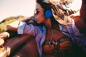 Young woman listening music with earphones during a road trip
