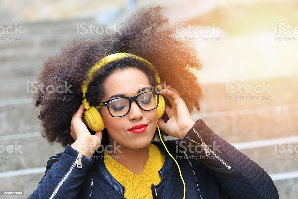 Young woman listening music with headphones on stairs stock photo