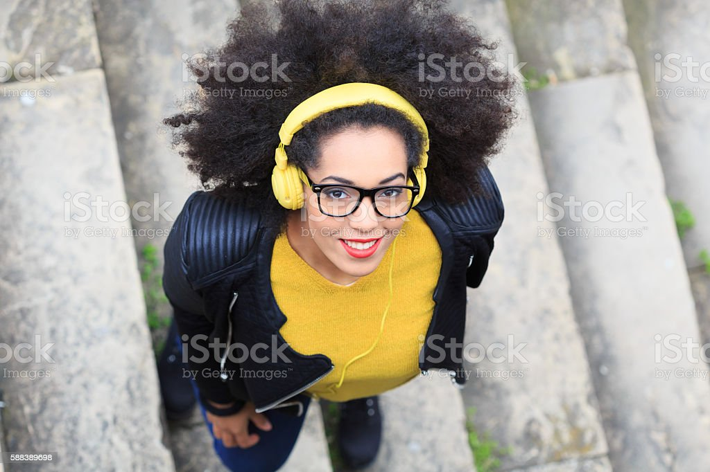 Young woman listening music with headphones standing on stairs stock photo