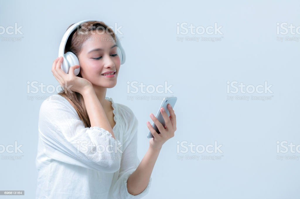 young woman listening music with wireless headphone, half latina and half asian stock photo