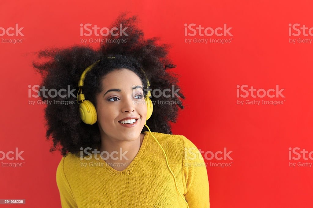 Young woman listening music with yellow headphones stock photo