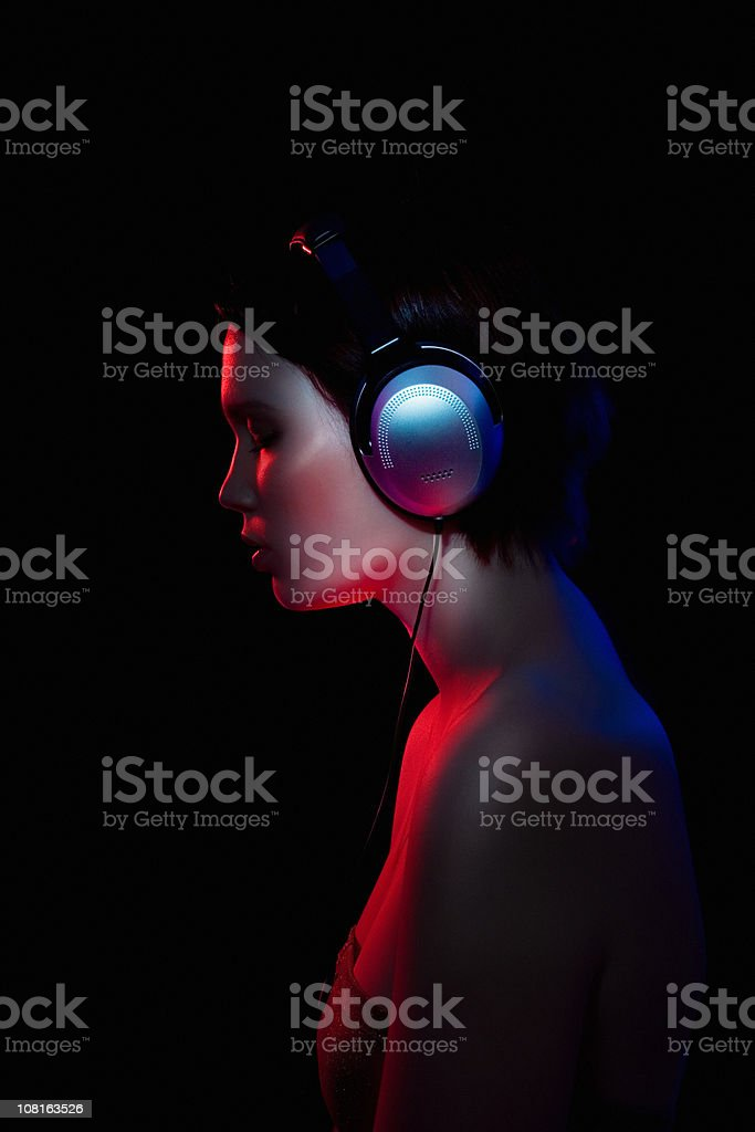 Young Woman Listening to Headphones in Dark royalty-free stock photo
