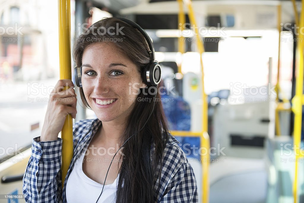 Young woman listening to her headphones on an empty bus stock photo