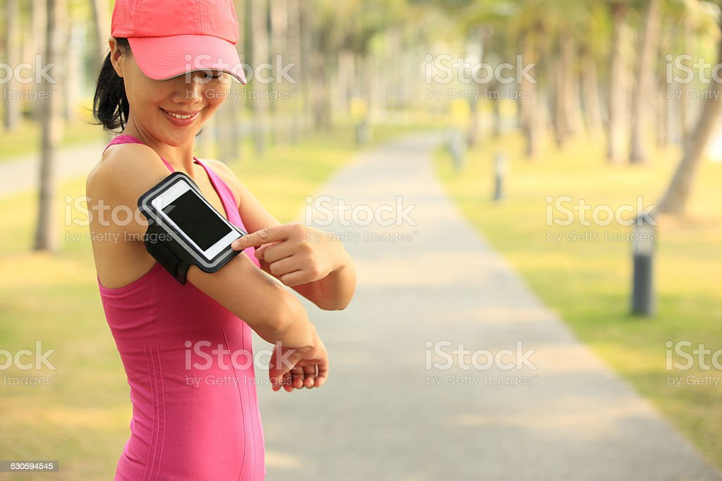 young woman listening to music from smart phone mp3 player stock photo