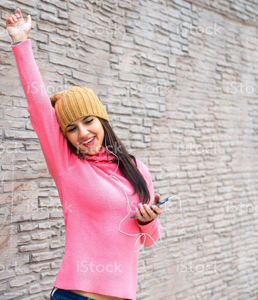 Young woman listening to music in headphones and dancing stock photo