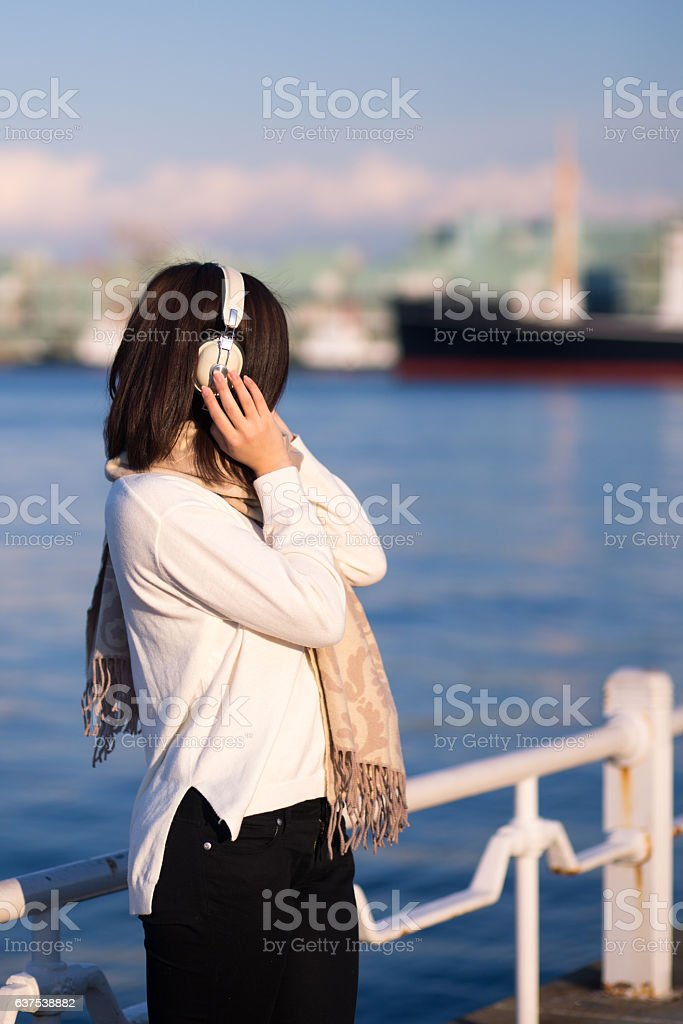 Young woman listening to music over headphones at harbor stock photo