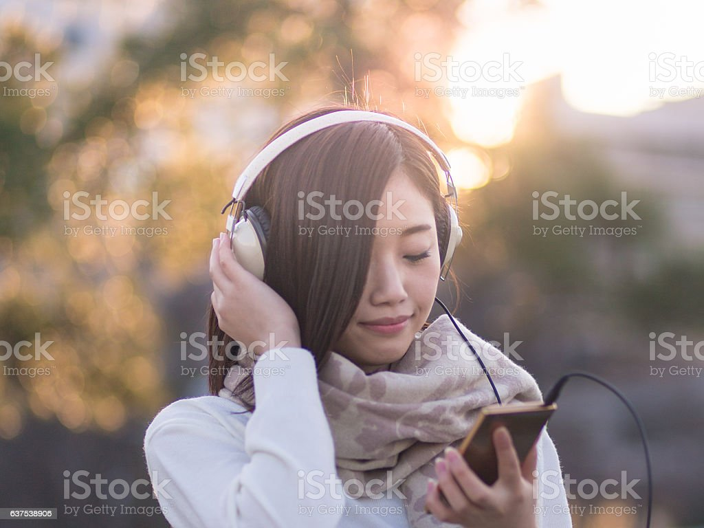 Young woman listening to music over headphones at park stock photo