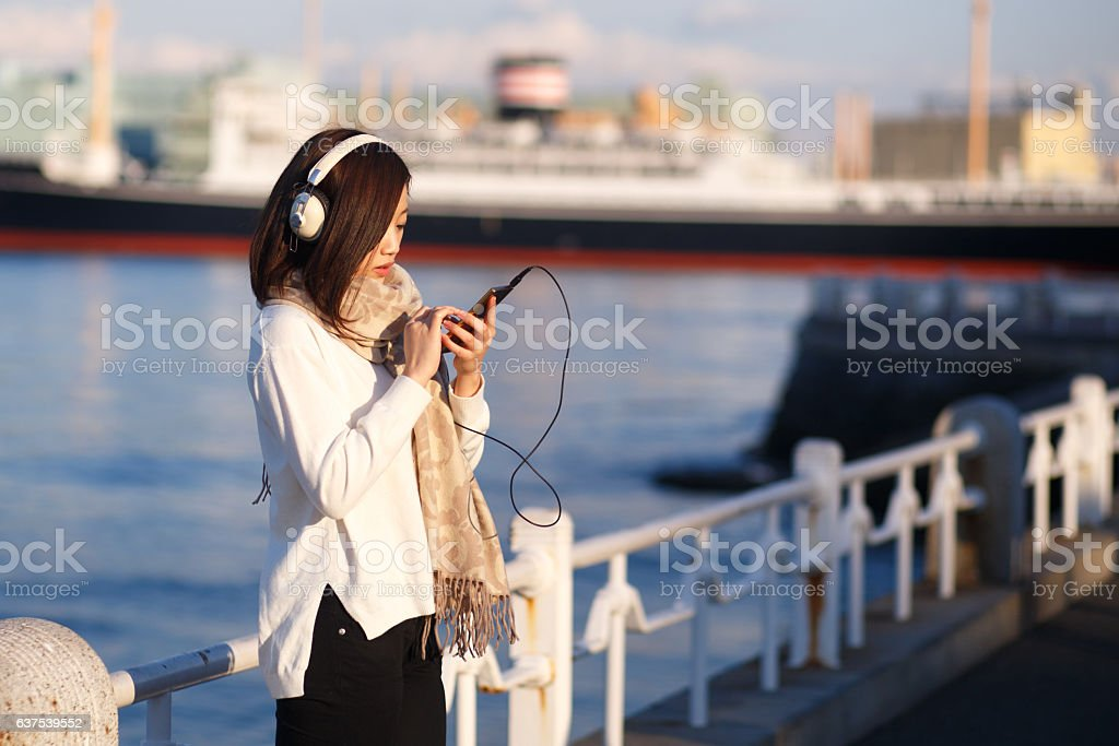 Young woman listening to music over headphones stock photo