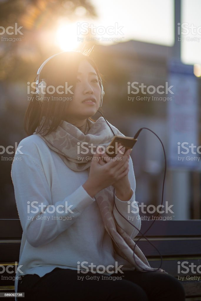 Young woman listing to music over headphones in twilight stock photo