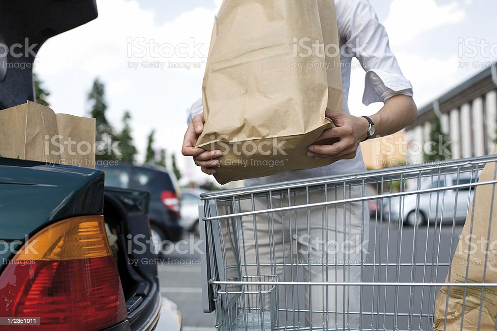 A young woman loads her groceries into her car stock photo