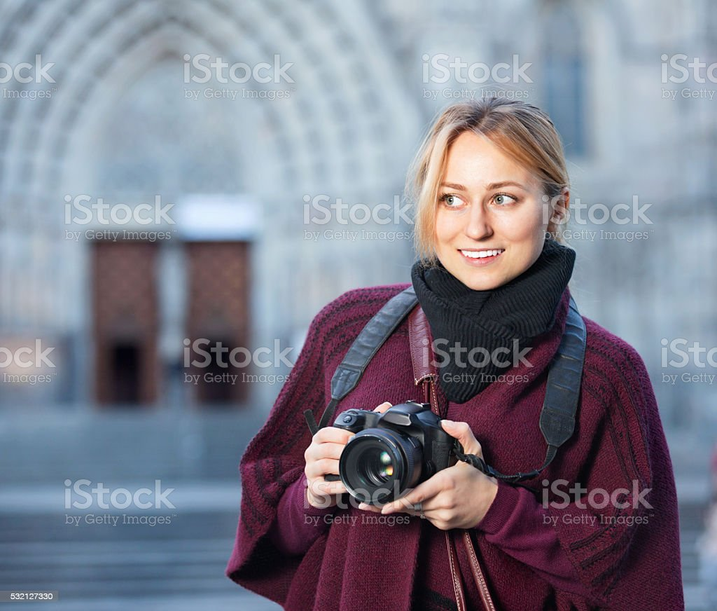 Young woman looking and taking pictures outdoors stock photo