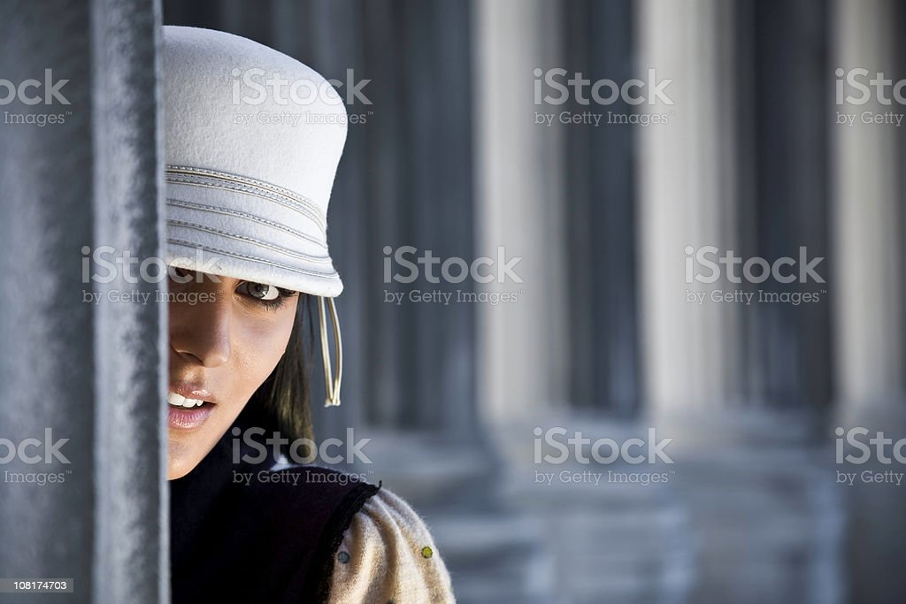 Young Woman Looking Around Corner Outside royalty-free stock photo