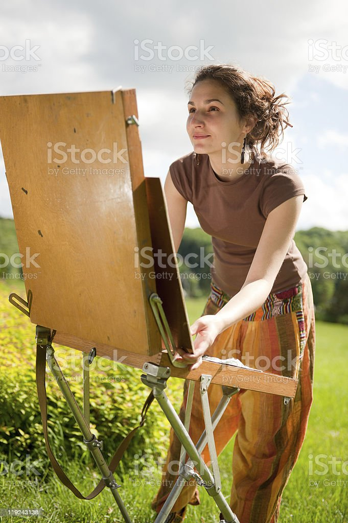 Young woman looking at a painting easel outside in a field royalty-free stock photo