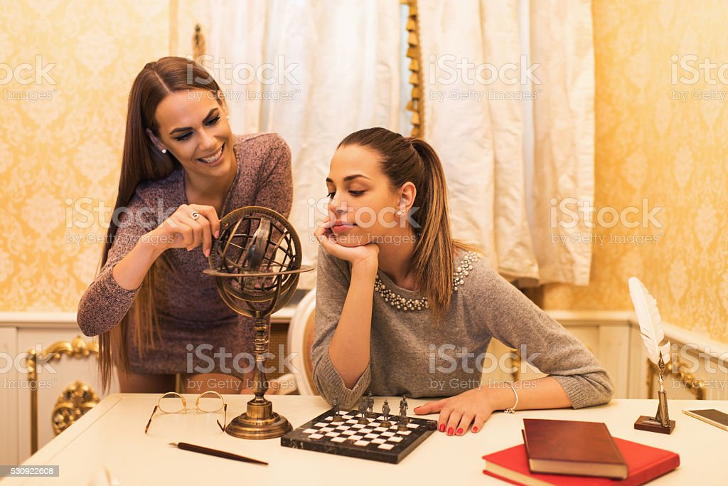 Young woman looking at armillary sphere with her friend. stock photo