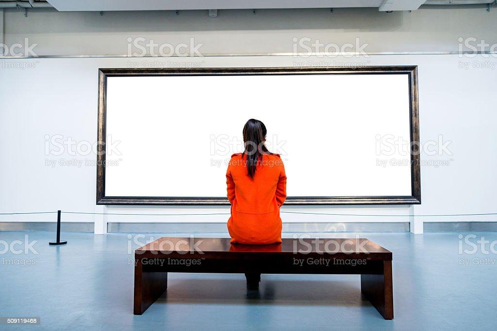 Young woman looking at artwork stock photo