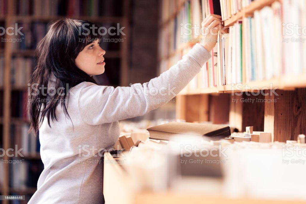 young woman looking at books in a bookstore stock photo