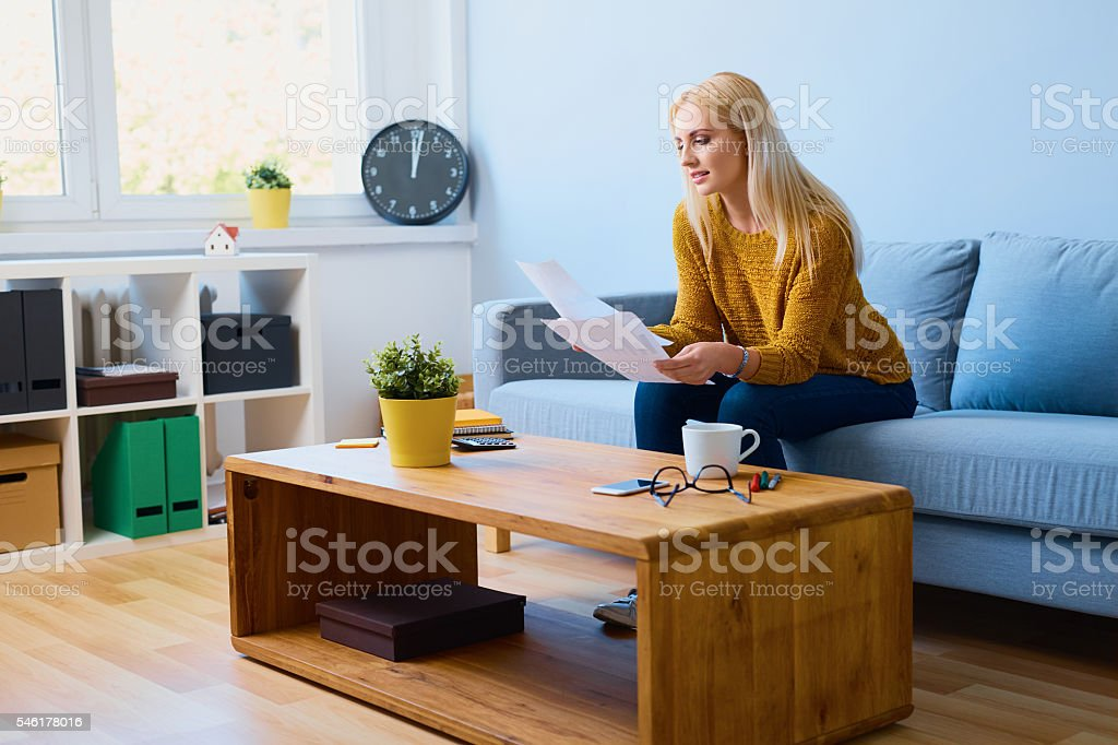 Young woman looking at documents at home, sitting on sofa stock photo