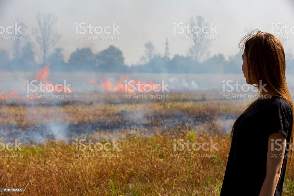 Young woman looking at fire at the field stock photo