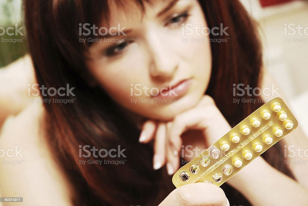 Young woman looking at her contraceptive pills stock photo