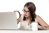 young woman looking at her laptop with a magnifying glass