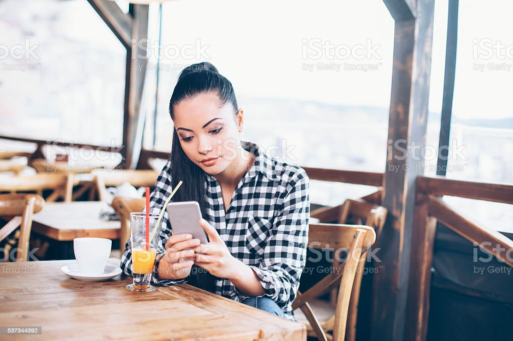 Young woman looking at her phone in the cafe shop stock photo