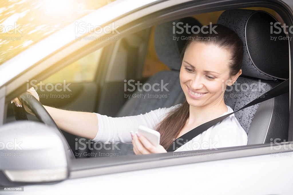 Young woman looking at her phone traveling by car stock photo