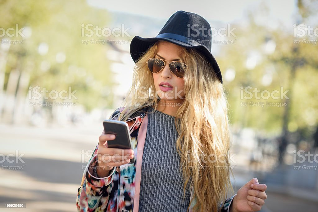 Young woman looking at her smartphone in urban background stock photo