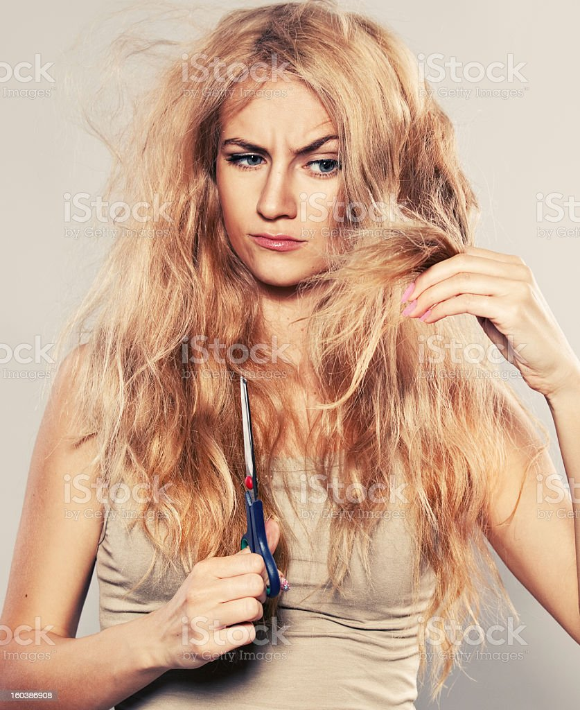 A young woman looking at her split ends in dismay stock photo