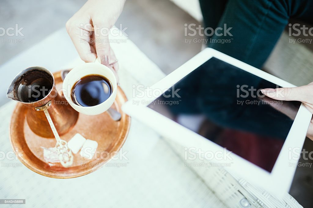 Young woman looking at her tablet, and drinking coffee stock photo