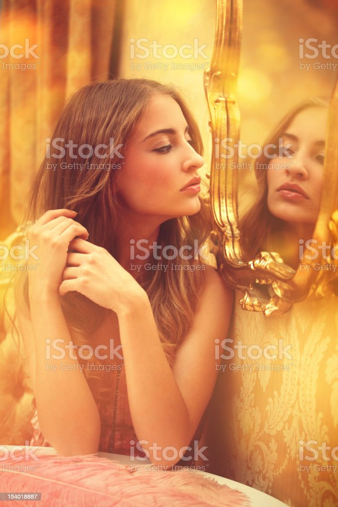 young woman looking at herself in a mirror stock photo
