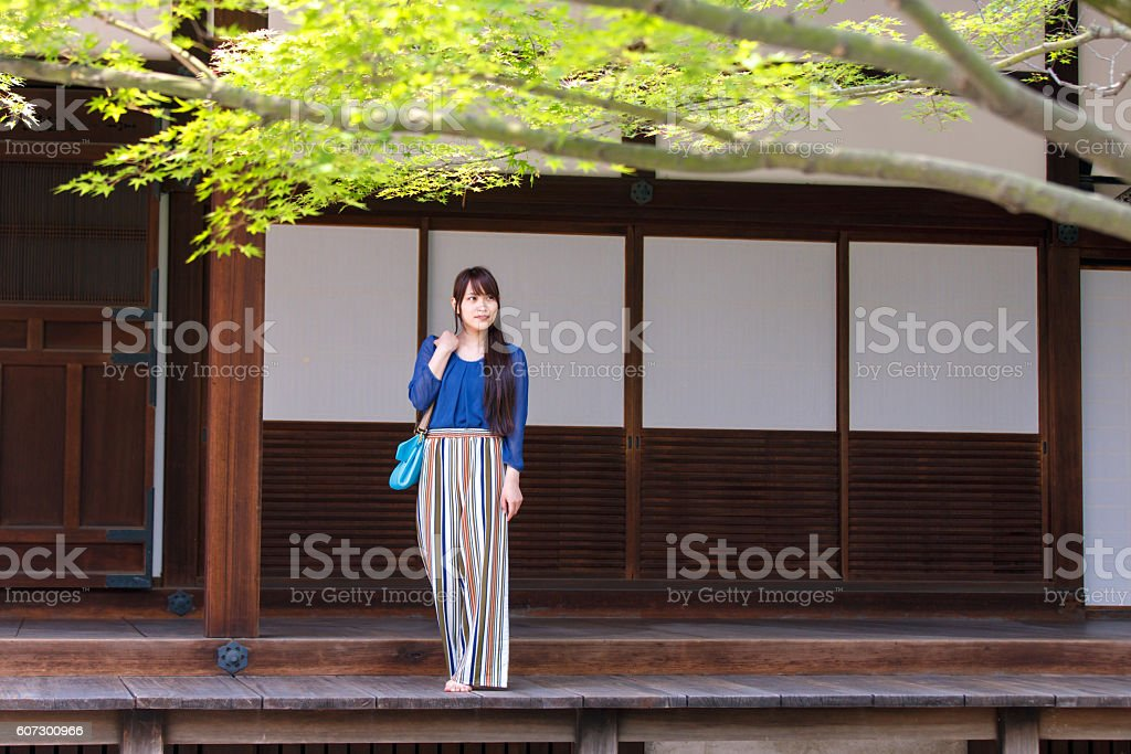 Young woman looking at Japanese garden from rich wood veranda stock photo