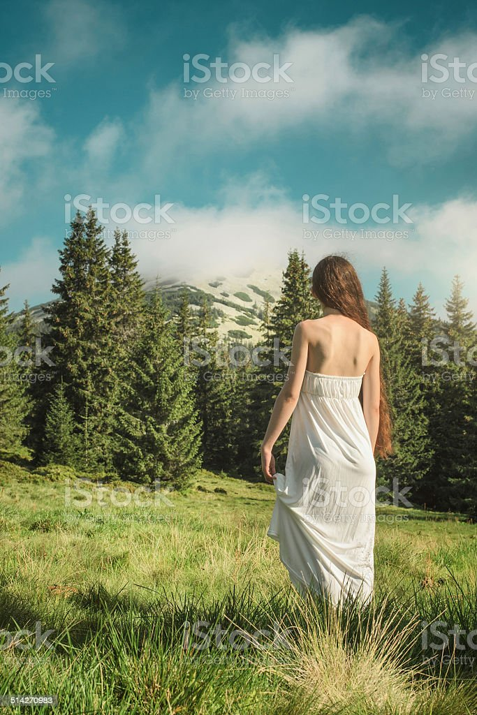 Young woman looking at mountain peak shrouded in clouds stock photo